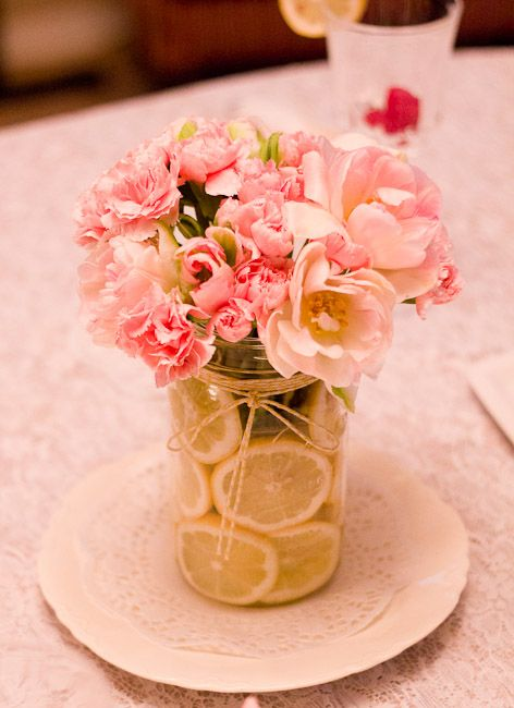 a jar filled with lemon slices and blush and pink flowers