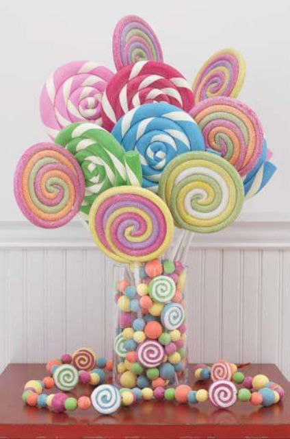 a whimsy centerpiece with various colorful candies in a jar and giant lollipops