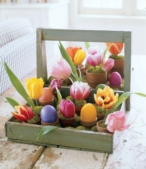 a wooden toolbox with pots with moss, dyed eggs and tulips