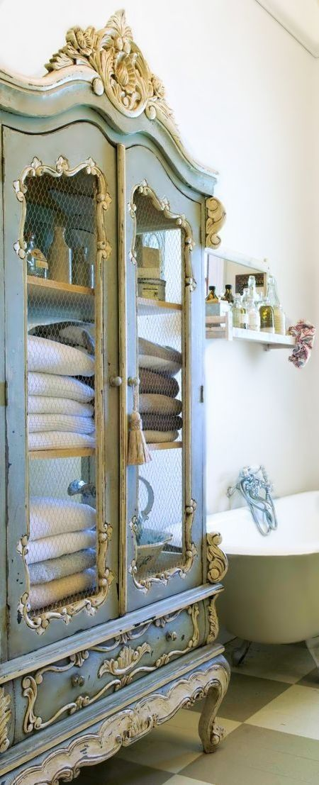 patina-covered armoire for towels and other bathroom stuff