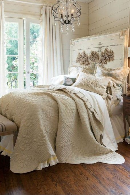 a bed with an oversized whitewashed headboard and a gorgeous crystal chandelier