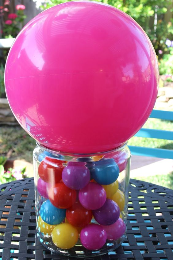 a colorful ball centerpiece in a jar and a pink balloon on top