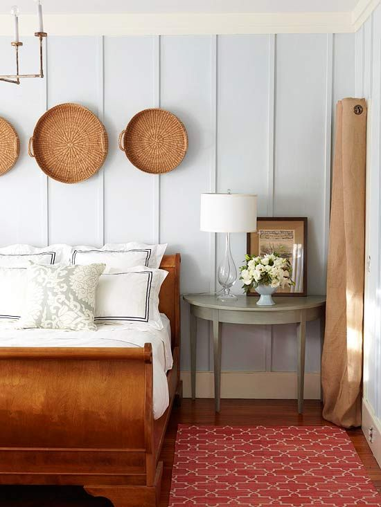 a cottage-style bedroom with baskets over the bed and a matching wooden bed