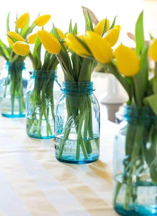 blue mason jars with fresh yellow tulips along the table