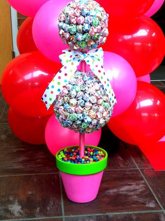 a double lollipop topiary in a pot filled with candies