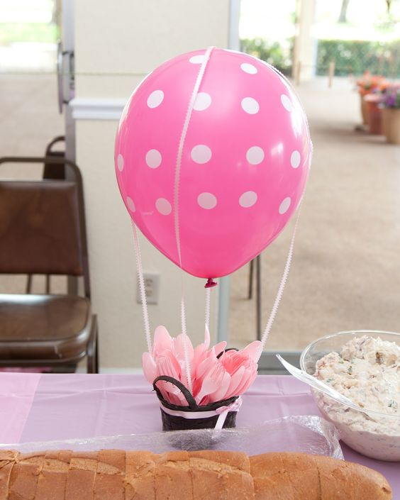 a pink polka dot centerpiece with plastic tableware is functional