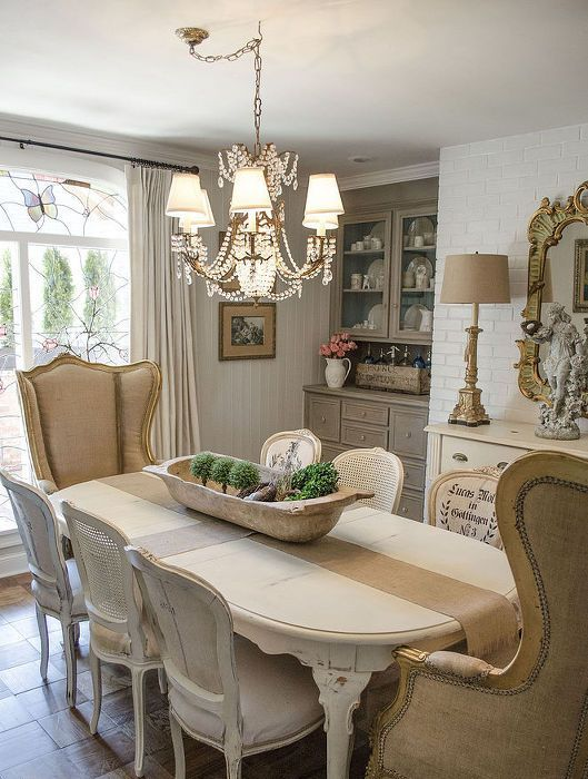a whitewashed table and chairs and some neutral amrchairs comprise a cool set