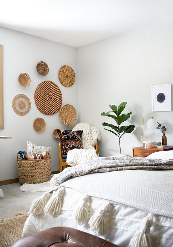 wall baskets and a storage one are used to emphasize the boho style of the bedroom