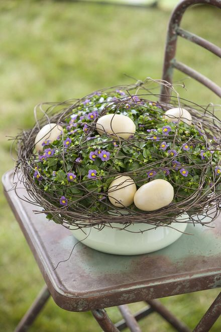 a bowl with greenery and flowers, with pastel eggs and twigs