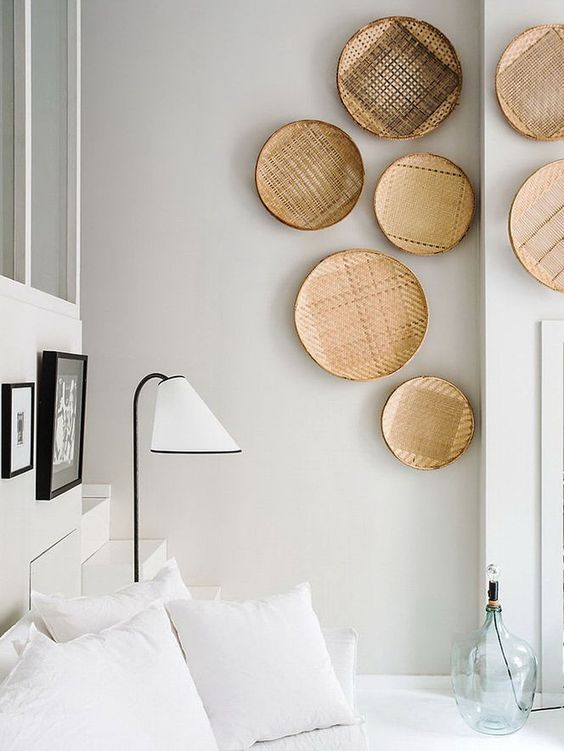 a crispy white bedroom is softened and warmed up with wall baskets