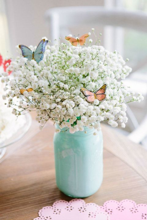 a mint colored mason jar with baby's breath and faux butterflies