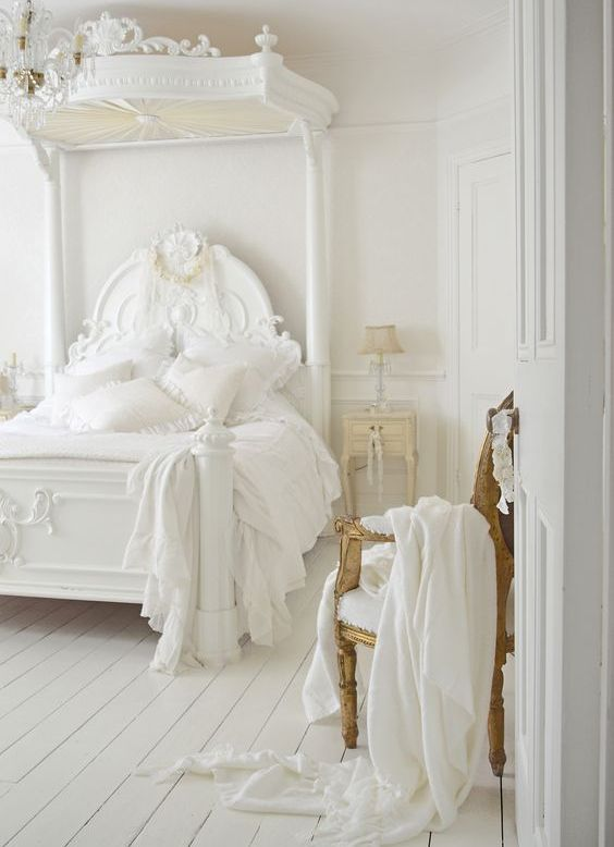 all-white space with a refined gilded chair, a gorgeous sculptural bed and creamy nightstands