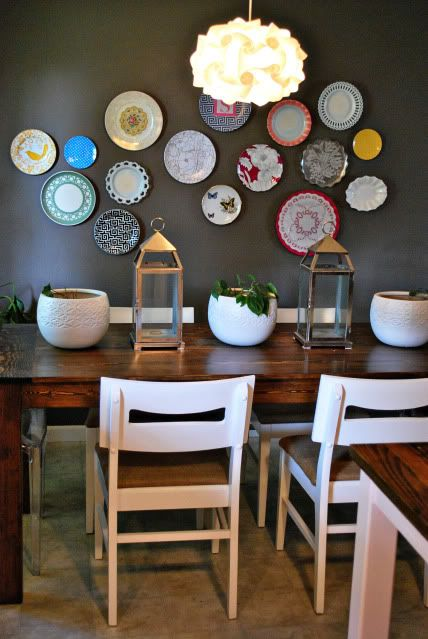 mismatching colorful plates on a dining room wall