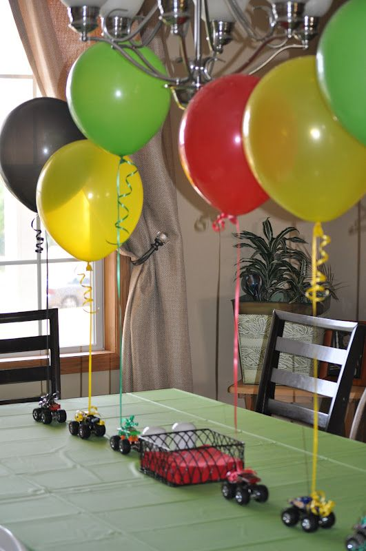 small toy cars with colorful balloons attached for a boy's party