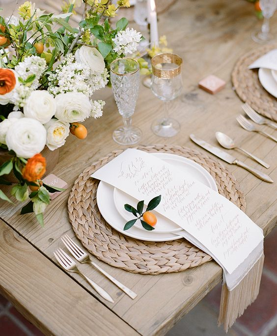 this tablescape is accentuated with creamy and orange flowers, fruit and a wicker placemat