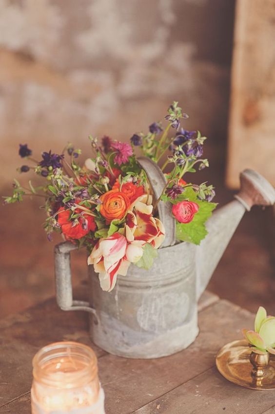 a shabby metal watering can with simple flowers