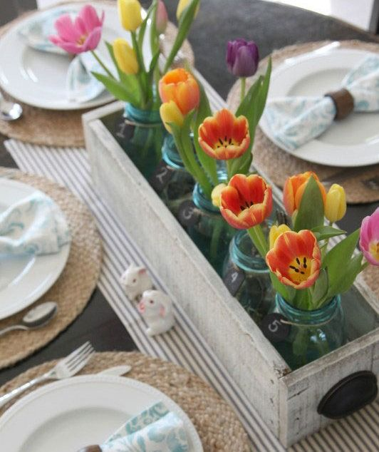 a wooden box with blue mason jars with fresh tulips inside