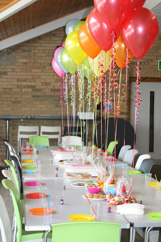 attach colorful balloons to the table to create floating decor