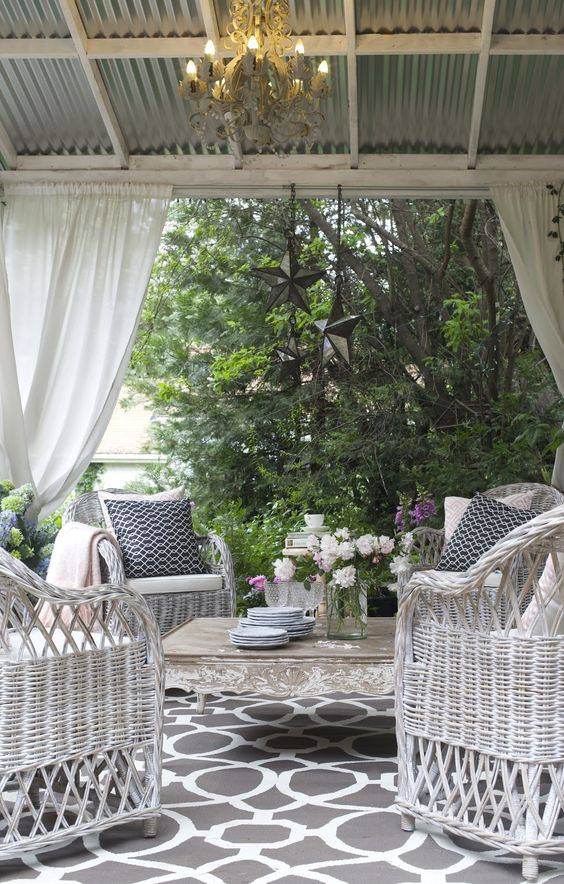 fresh and inviting patio design with white wicker furniture and a vintage coffee table