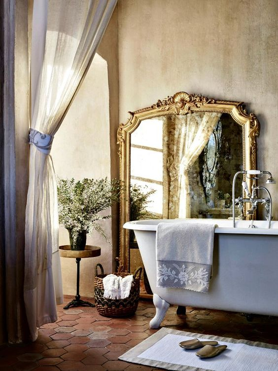 lavender painted clawfoot bathtub and an oversized refined mirror