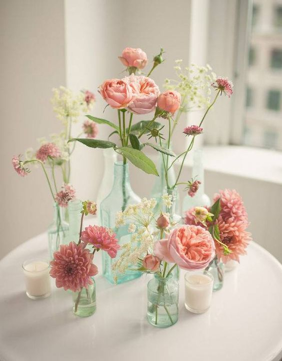 simple pink flower arrangement in different bottles and vases