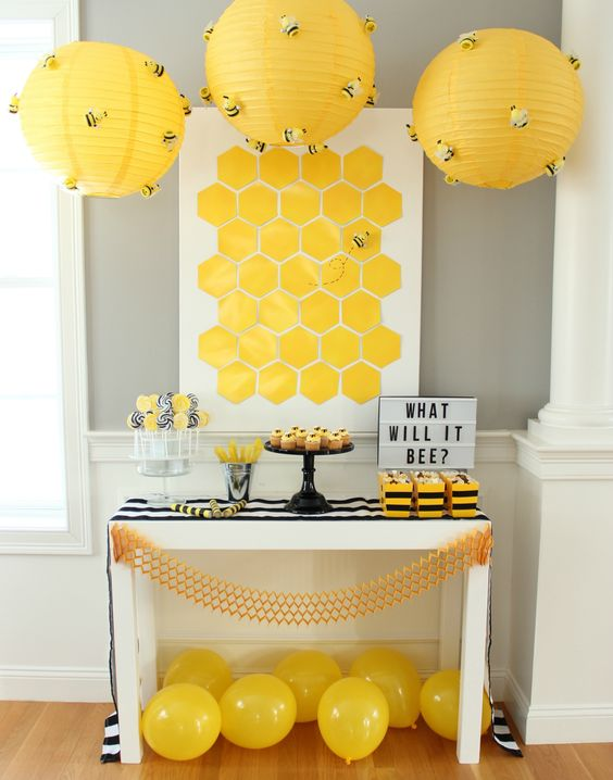 yellow lanterns with bees attached over the dessert table