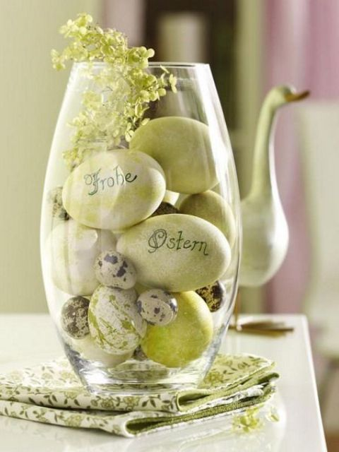 a glass jar with green dyed eggs of different sizes and some greenery