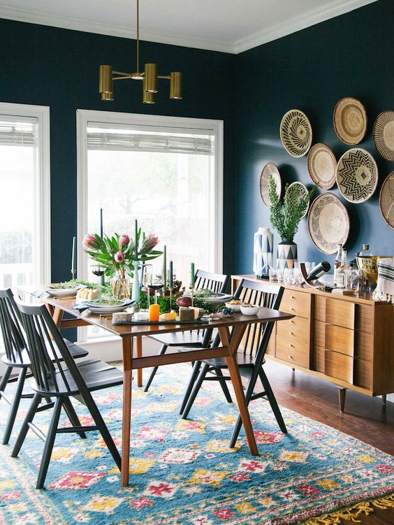 a mid-century modern dining space and wall baskets to soften the dark walls