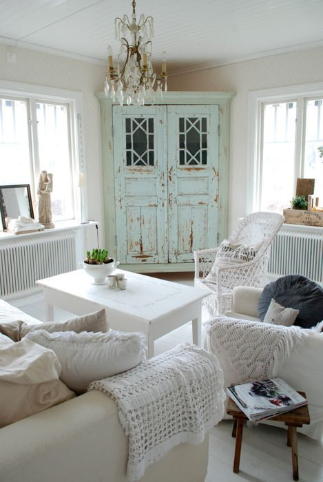 a mint-colored shabby chic armoire is a statement piece in this white space