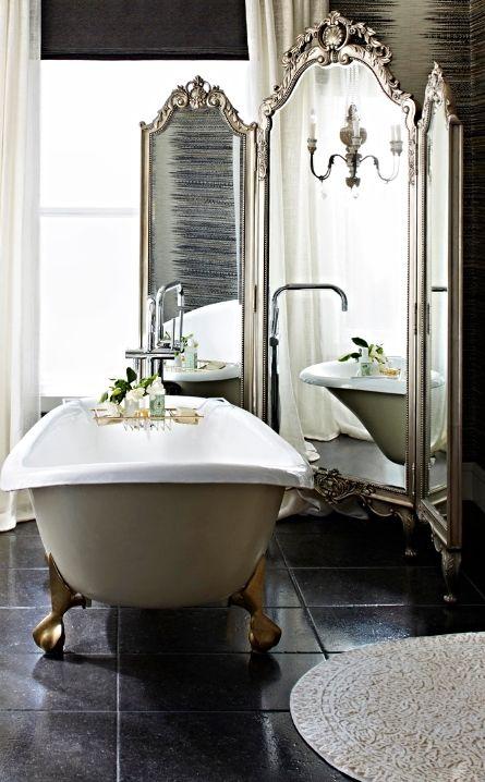 a vintage clawfoot bathtub and a triple mirror behind it