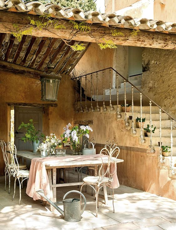 large farmhouse table and white forged chairs, a large lantern over them