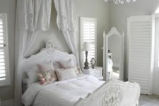 14 serene all-white space with a refined bed and a vintage floor mirror
