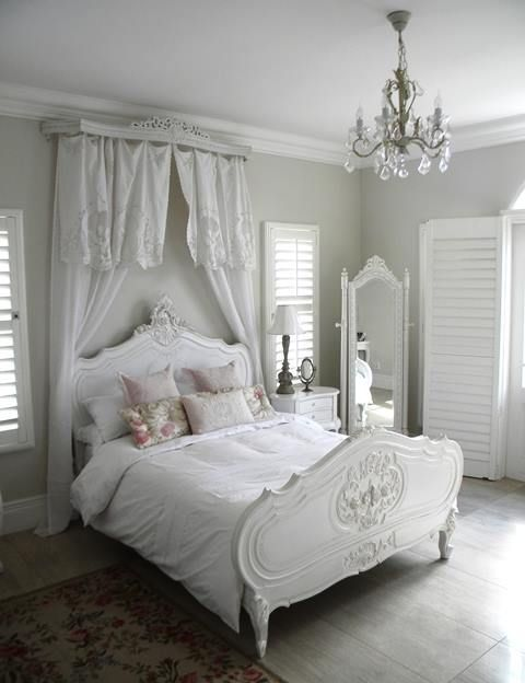 serene all-white space with a refined bed and a vintage floor mirror