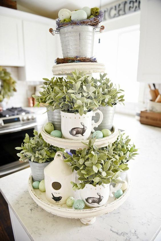 a cupcake stand with vintage cups with greenery and speckled eggs