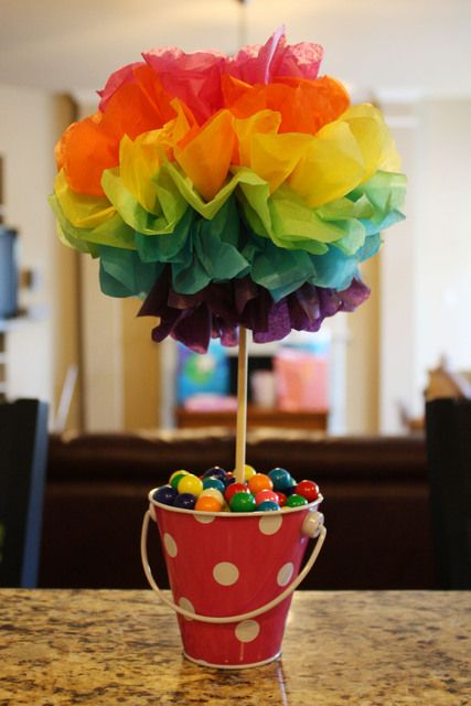 a small bucket with colorful candies and a colored paper topiary