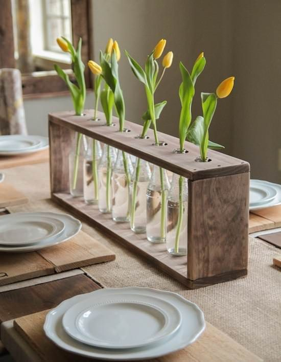 a frame of repurposed pallets with bottles and single tulips in each