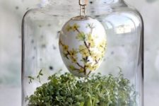 16 a large jar with greenery and a dyed egg hanging on a willow branch