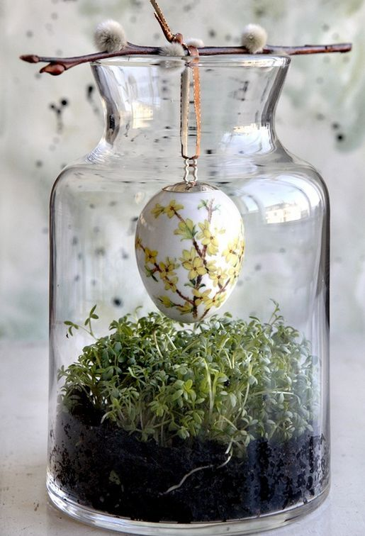 a large jar with greenery and a dyed egg hanging on a willow branch
