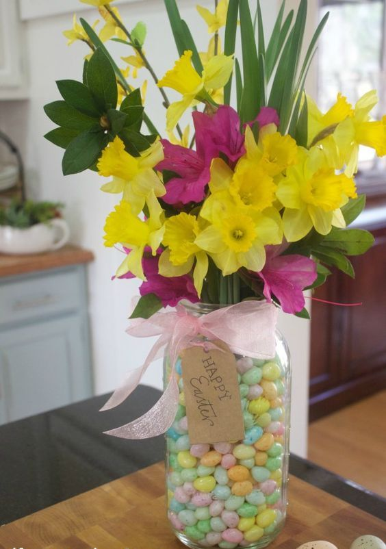 a mason jar with colorful candies and some bold fresh flowers