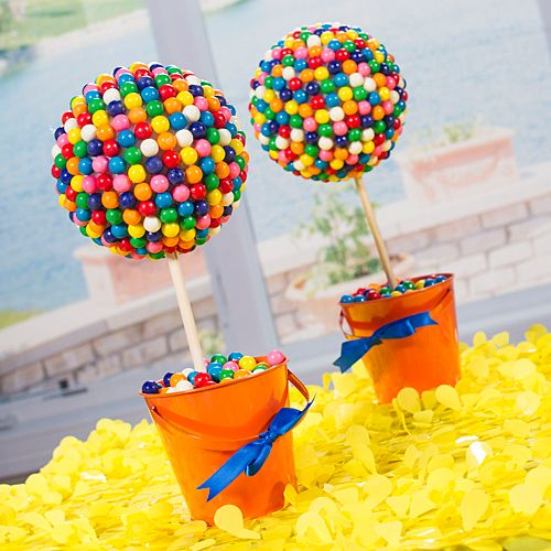 orange buckets filled with colorful candies and gumball topiaries