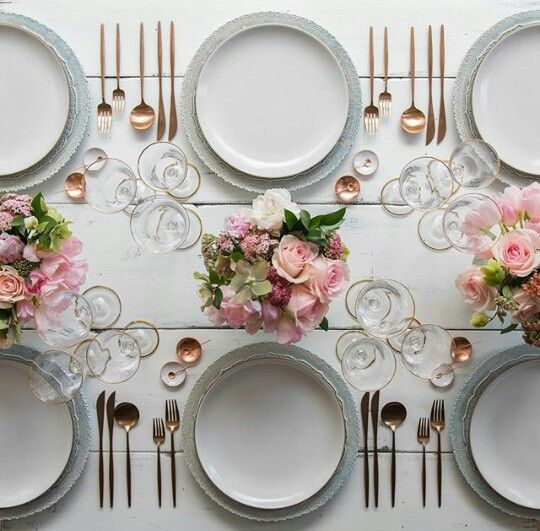 the tablescape is neutral but with pink centerpieces and glam gold cutlery