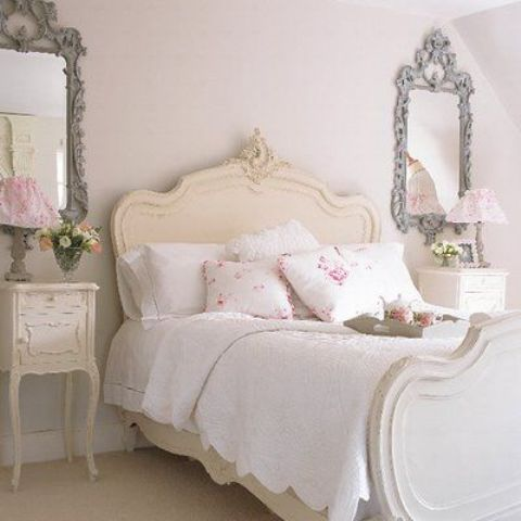 vintage framed mirrors, bedside tables and a cream colored bed give a tone to the whole space