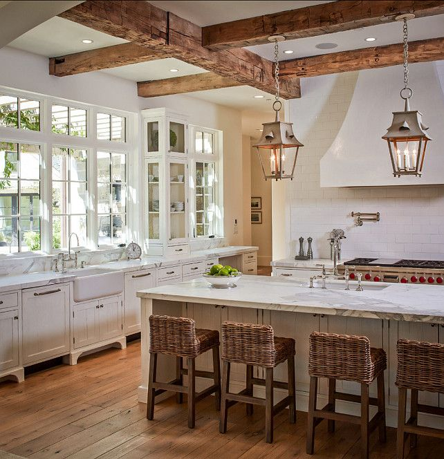 wooden beams with hanging lanterns and wicker chairs add interest and coziness to the kitchen