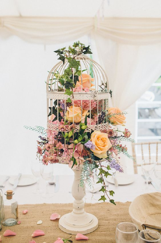 a bird cage on a stand filled with various blooms and leaves