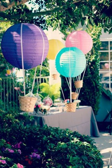 colorful hot air balloons as decor for an outdoor baby shower