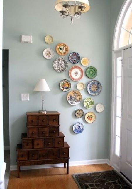 curved colorful plate arrangement in an entryway, with different patterns and images