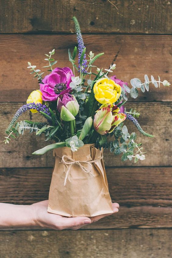 a colorful bouquet with eucalyptus in a vase with a paper sack