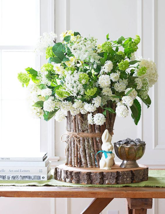 a white hydrangea centerpiece with a vase decorated with sticks and twine on a wooden slice