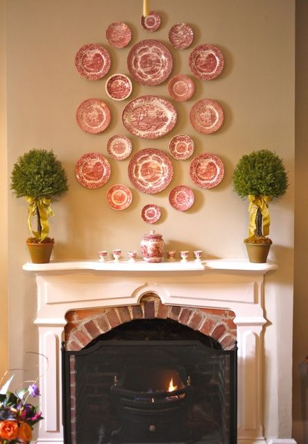 matching red and white plates in different sizes over the fireplace