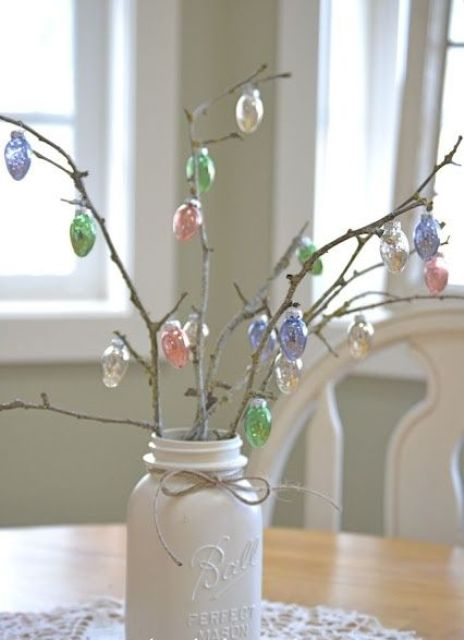 a mason jar with branches and Easter egg ornaments on them